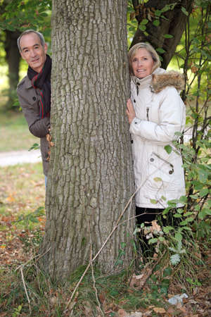 55 60 years: Couple standing behind a tree trunk