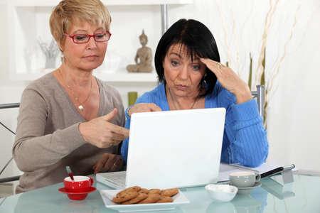 technophobe: Older women puzzling over a laptop