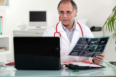 doctor appointment: Senior doctor checking an x-ray in his office Stock Photo