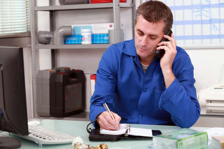 Plumber taking a call in an office and making an appointment in his diary