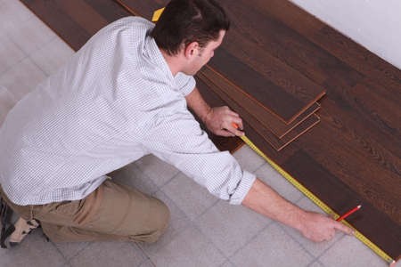 kneeling man: Man measuring wooden flooring Stock Photo