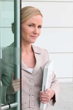 Mujer rubia con un ordenador portátil en sus brazos