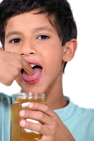 saliva: Boy tasting some honey Stock Photo