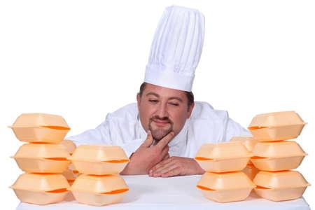 hesitating: Cocine entre cajas de hamburguesas Foto de archivo