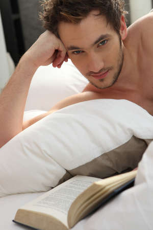 Young man reading a book in bed photo