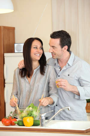 perfect housewife preparing meal with husband by her side photo
