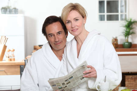 bath robes: Couple reading the newspaper Stock Photo