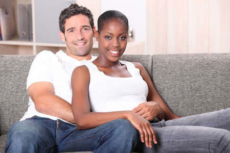 mixed race couple: Pareja de raza mixta sentado en el sof�