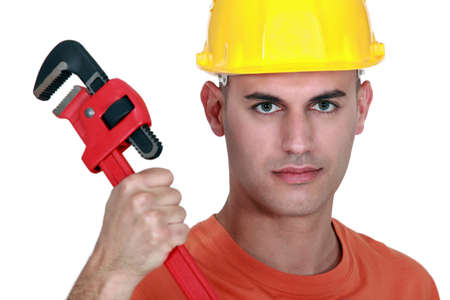 Tradesman holding a pipe wrench photo