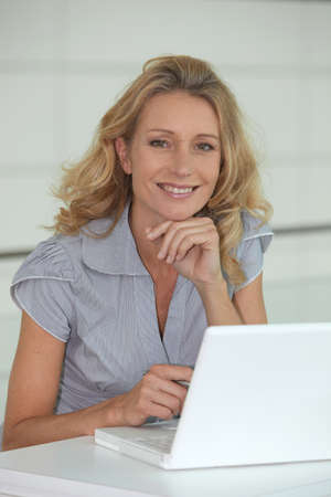 Blond woman sat at desk with laptop computer photo