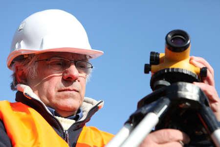 cartographer: mature surveyor in construction site