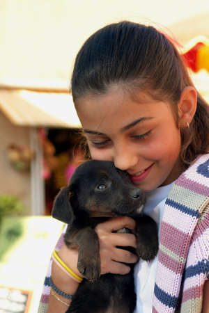 cuddly: Young girl hugging a puppy