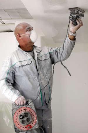 пыль: Человек шлифования гипсокартонные потолки Фото со стока