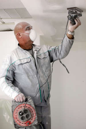 dust mask: Man sanding a plasterboard ceiling Stock Photo