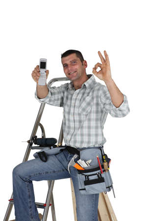 Carpenter with mobile giving the OK photo