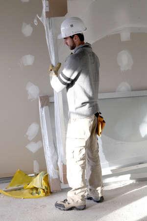 plasterboard: Man carrying sheet of plaster board Stock Photo