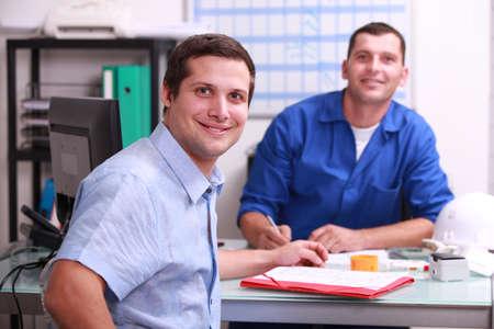 manufactura: dos colegas hombres sentados en una oficina sonriendo y mirando a la c�mara Foto de archivo