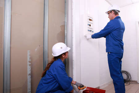 distribution board: Electricians installing a distribution board Stock Photo