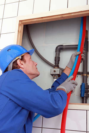 jumpsuite: 45 years old plumber connecting pipes