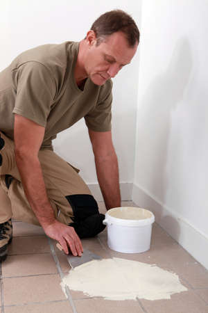 45 49 years: Man spreading adhesive over old floor tiles