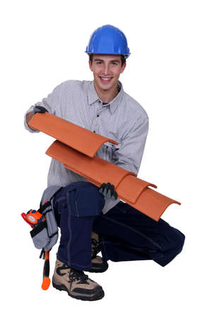 Worker holding roof shingles photo