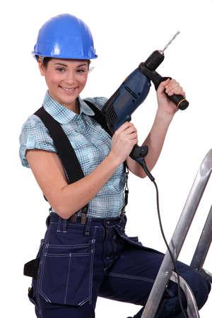 head collar: Tradeswoman holding a power tool Stock Photo