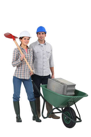 Couple transporting building blocks in wheelbarrow Stock Photo - 11934713