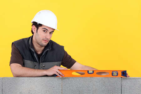 Builder with a spirit level on a wall photo