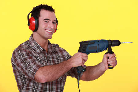 anti noise: Man with a power drill Stock Photo