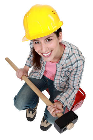 sledge hammer: Woman with sledge-hammer sitting on tool box Stock Photo