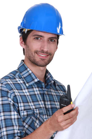 Foreman holding radio and plans photo