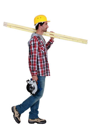 year profile: Tradesman carrying wooden planks and a circular saw Stock Photo