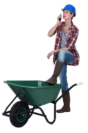 Tradeswoman speaking into a walkie-talkie and propping her foot up on a wheelbarrow photo