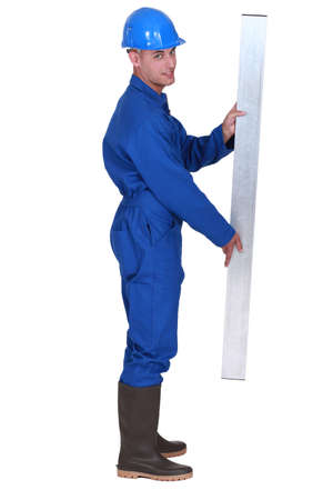 steadiness: Man stood holding metal beam Stock Photo