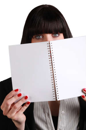 woman hiding behind wire-bound notebook photo