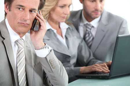 collaborators: Man on cellphone whilst colleagues use laptop
