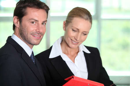 Businessman and woman looking at folder photo