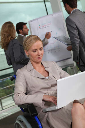 Female executive in wheelchair using laptop computer Stock Photo - 11935013