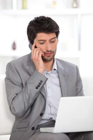 dark haired: Dark haired man working from home Stock Photo