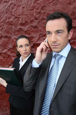 watchfulness: a manager at phone and his assistant