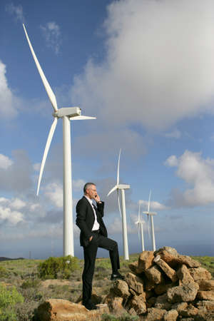 Man using a mobile phone next to wind turbines photo