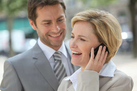 45 50 years: Businessman and woman laughing on the phone.