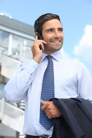 Businessman speaking on a cellphone outside an office building Stock Photo - 11935075