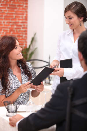 portrait of a waitress with couple at restaurant photo