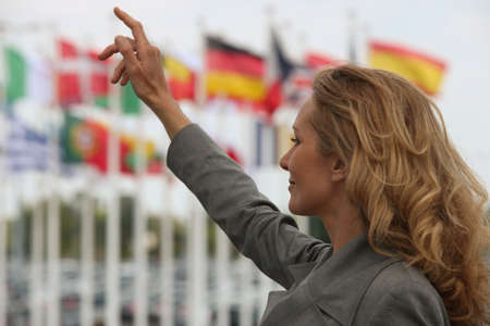 summoning: Woman hailing a taxi in front of international flags