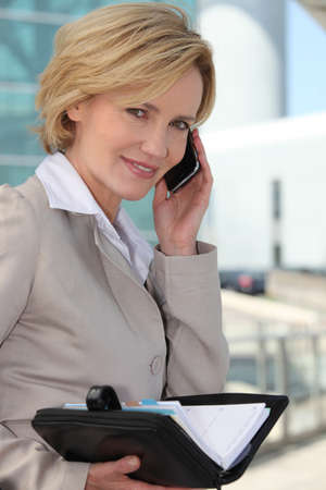Businesswoman checking her diary smiling photo