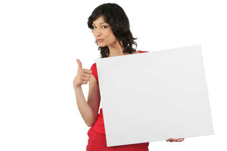 Attractive woman giving the thumbs up to a board left blank for your message photo