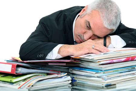 exasperate: Man lying on paperwork