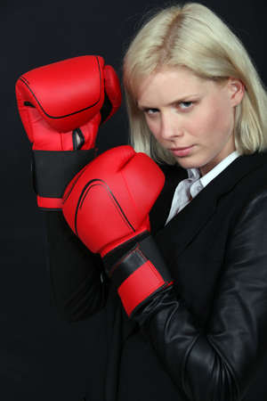 Businesswoman holding boxing gloves photo