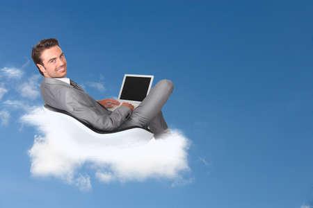 Uomo d'affari seduto su una nuvola con il suo laptop